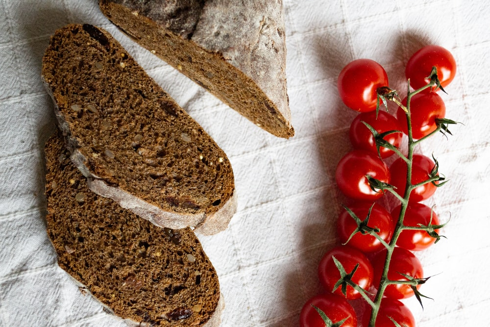 red cherry tomatoes beside sliced bread on white textile