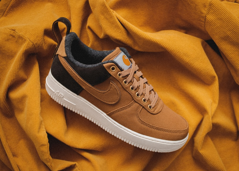 brown Nike sneaker on yellow textile
