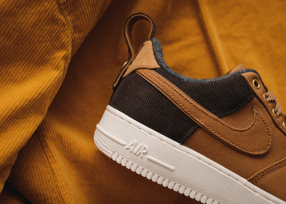 close-up photography of brown and white Nike Air Force 1 low