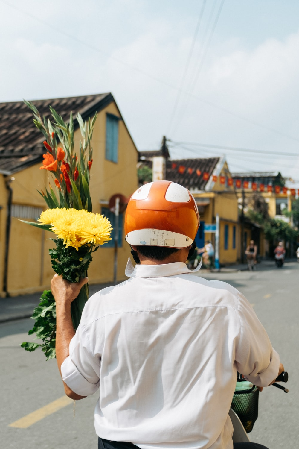 person riding motorcycle while holding yellow petaled flowers during daytime