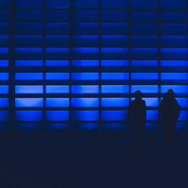 silhouette photo of two person standing near wall