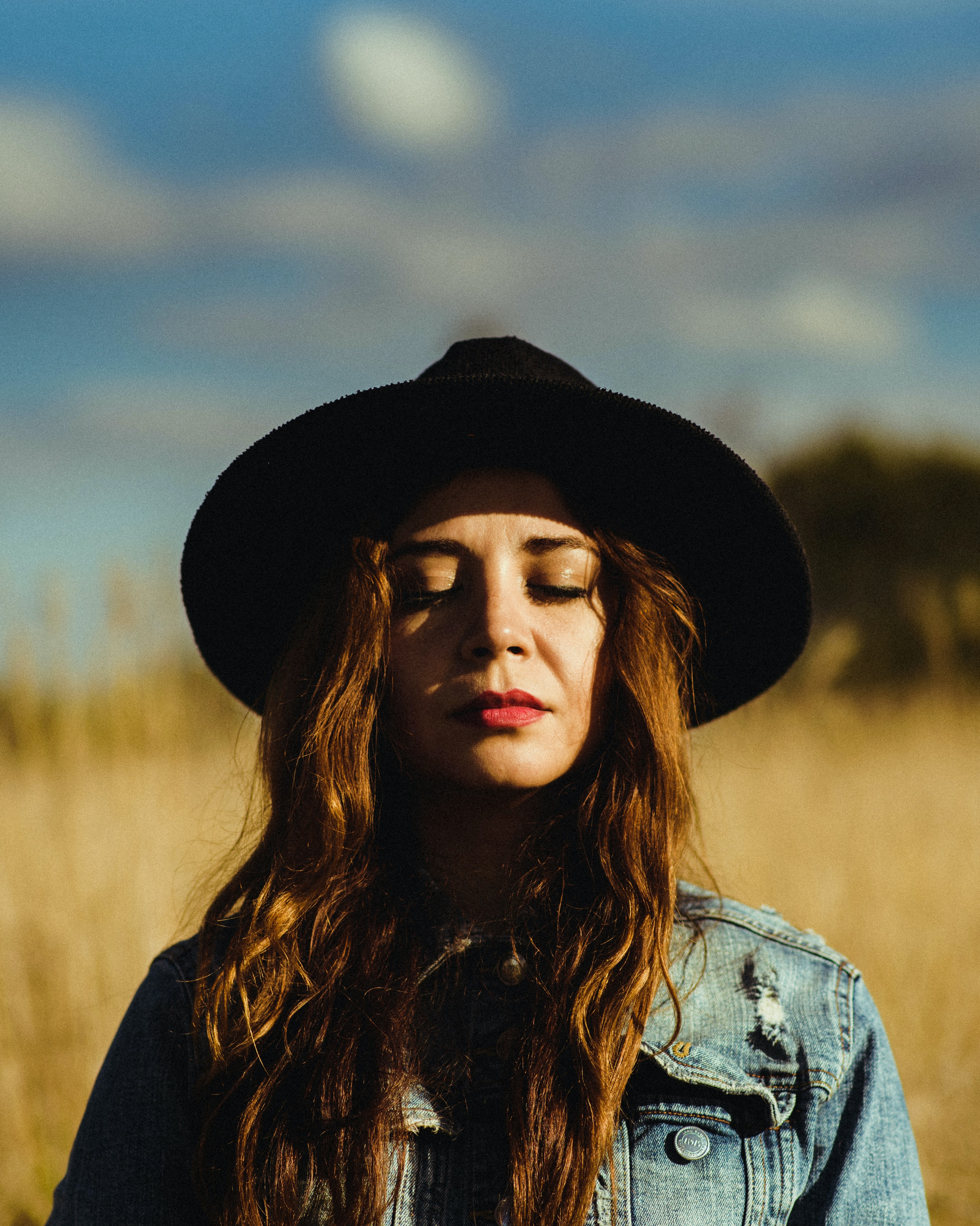 selective focus photography of woman closing her eyes wearing black sun hat and blue denim jacket