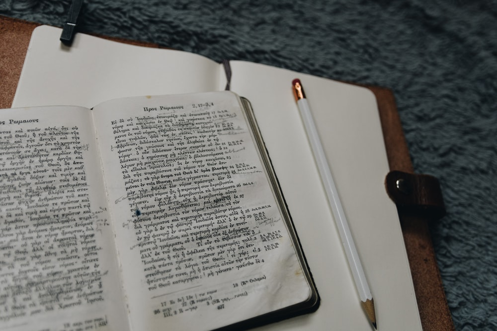 white pencil beside book