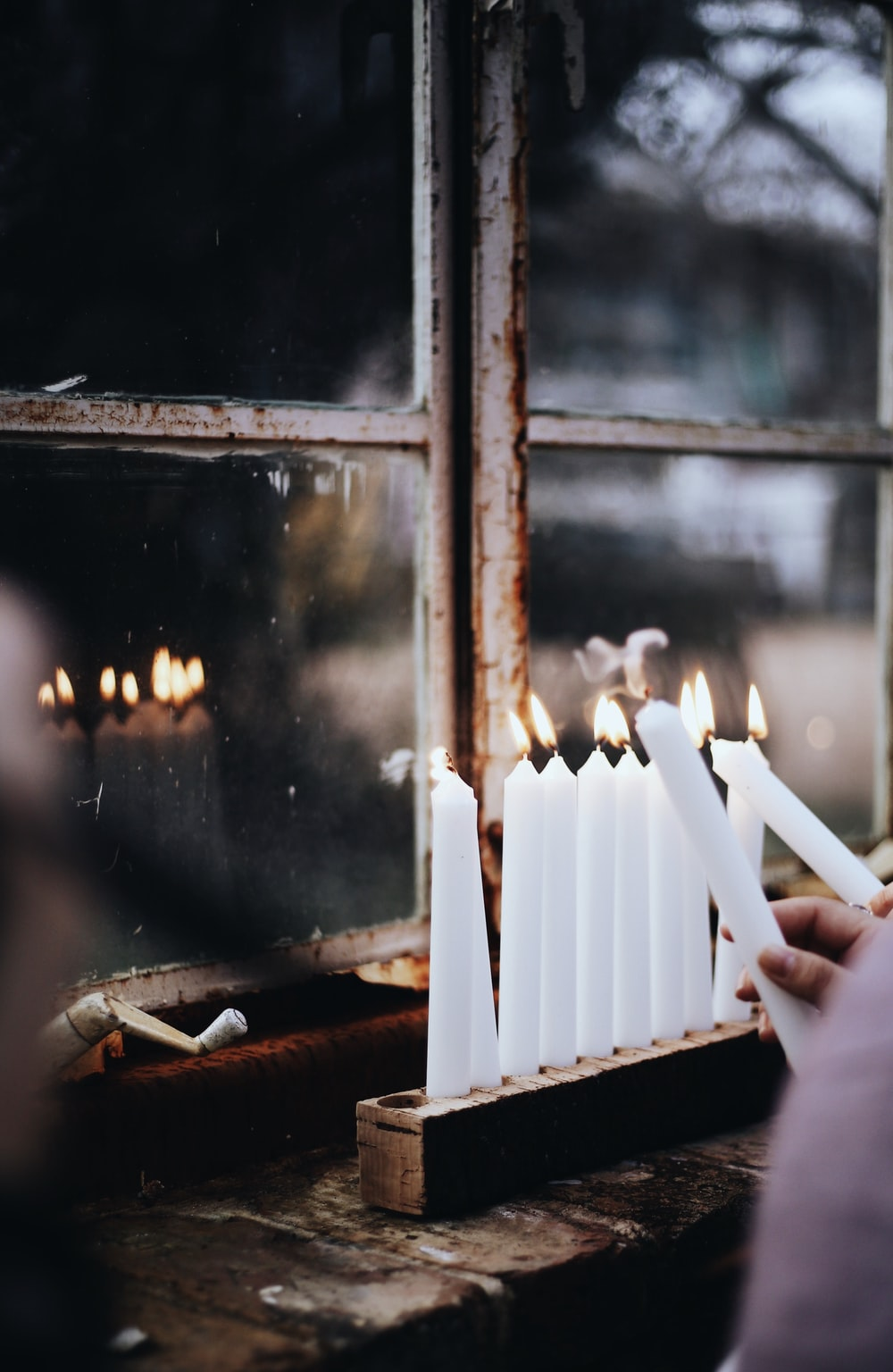 person lighting white candlesticks in a rack near glass windowpane