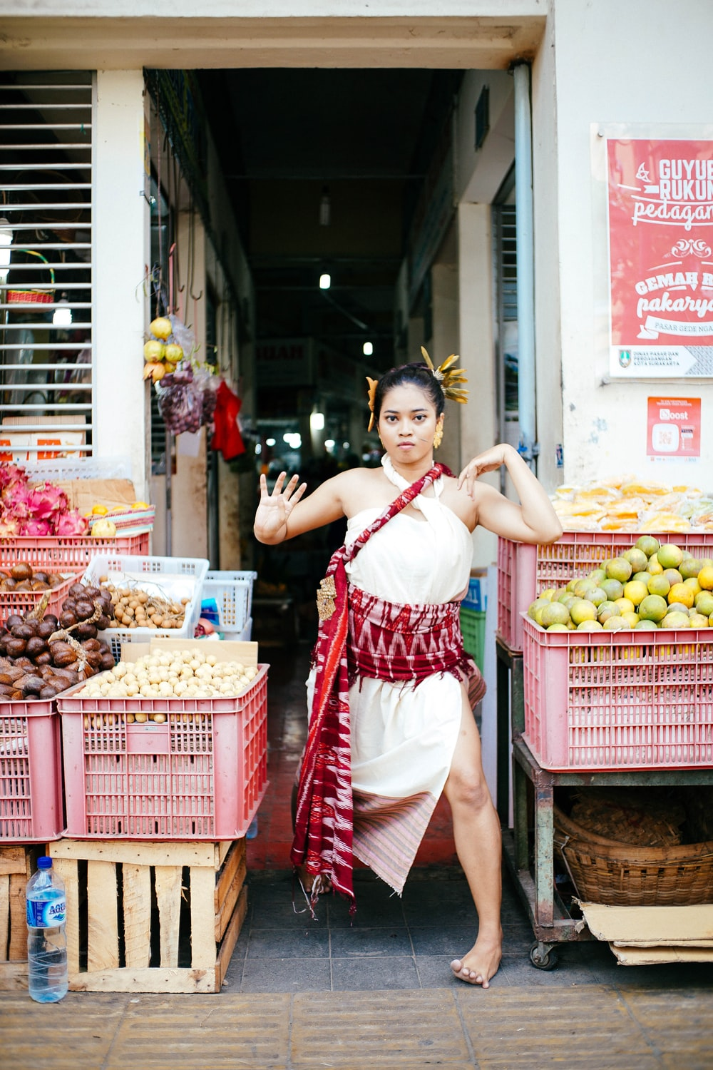 woman standing beside crates of fruits