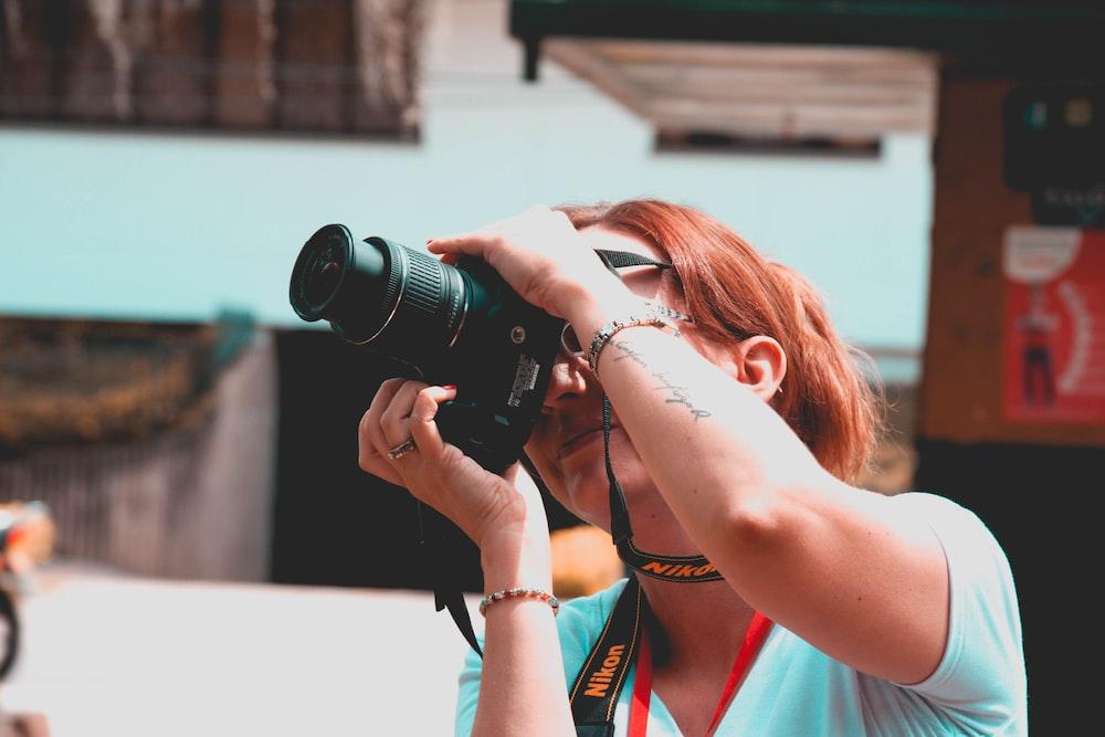 woman using black Nikon DSLR camera