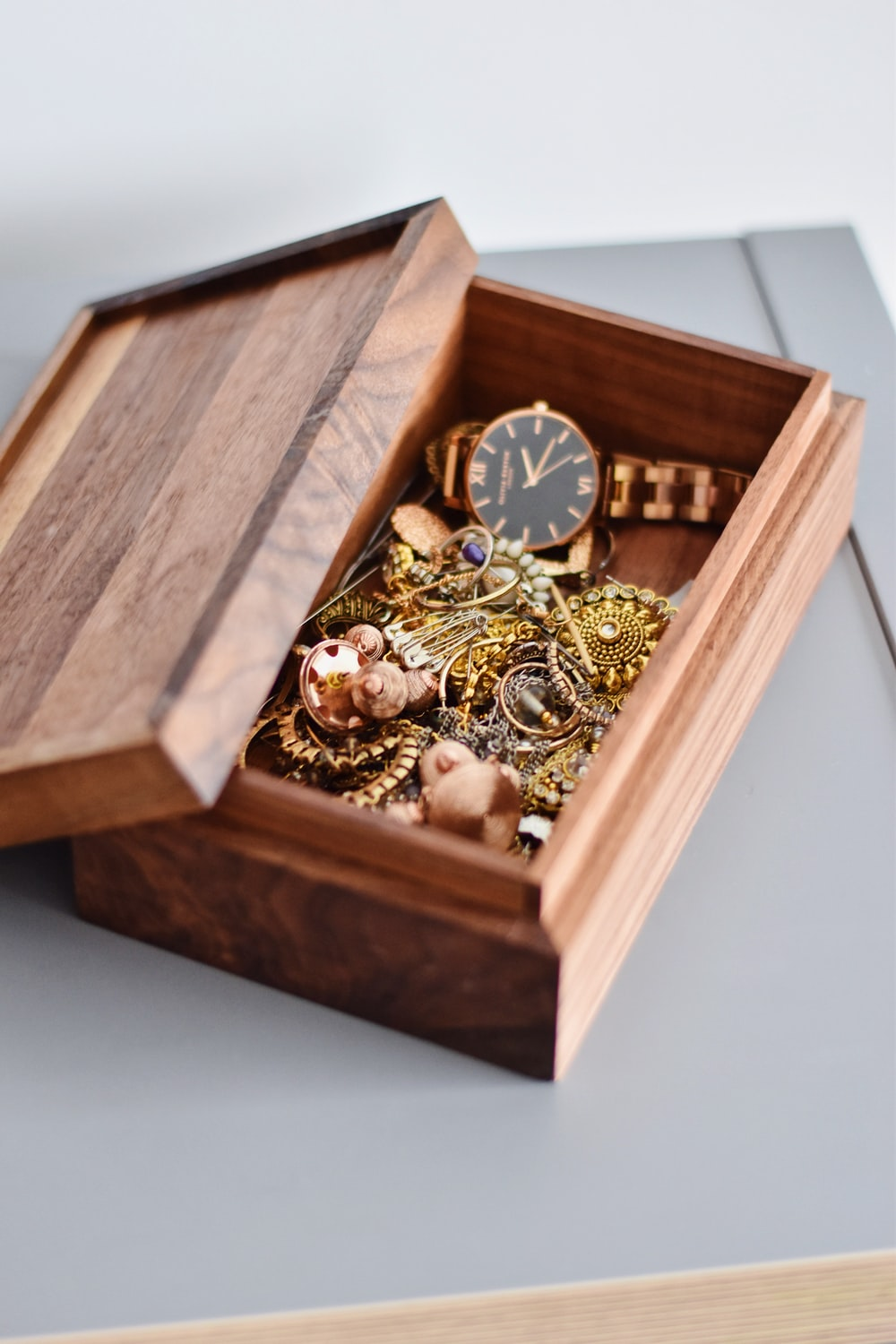 gold watch and pendant on brown wooden box