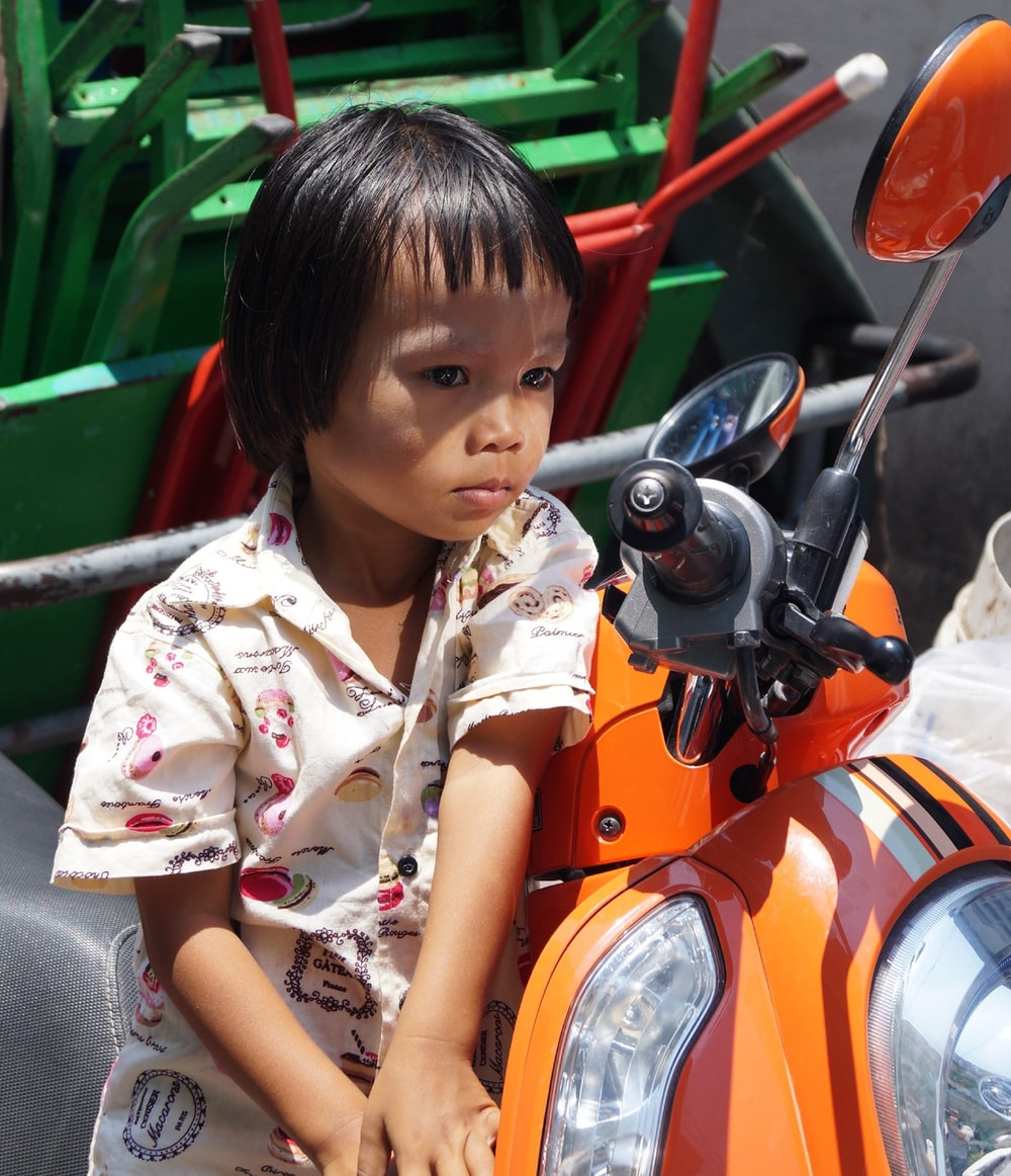 child in white top leaning by motor scooter at daytime