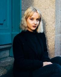 woman in black jacket wearing jacket sitting beside wall