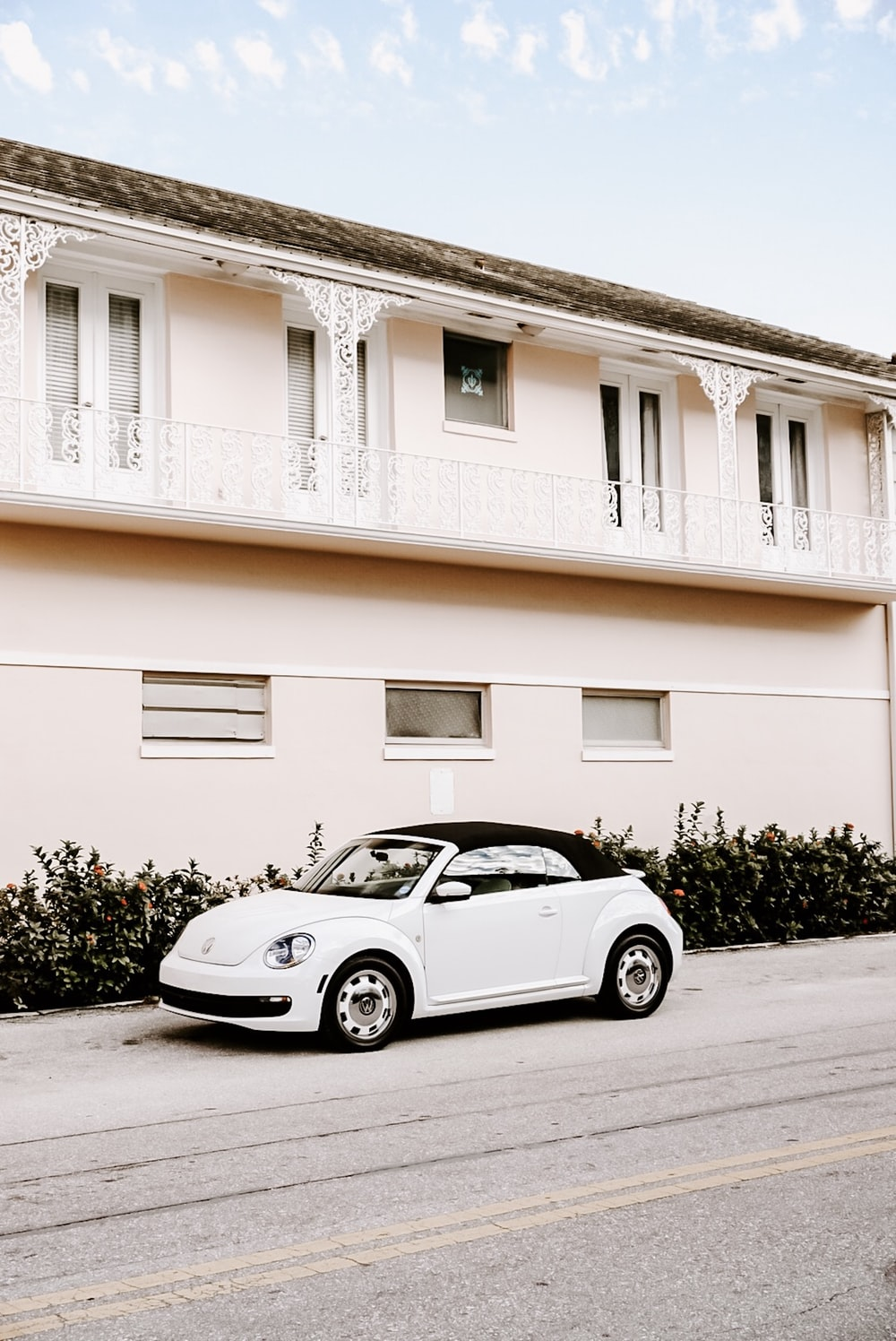 white Volkswagen New Beetle convertible parked near concrete building during daytime