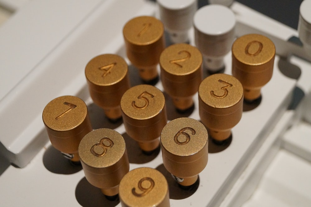 brass-colored and white number buttons