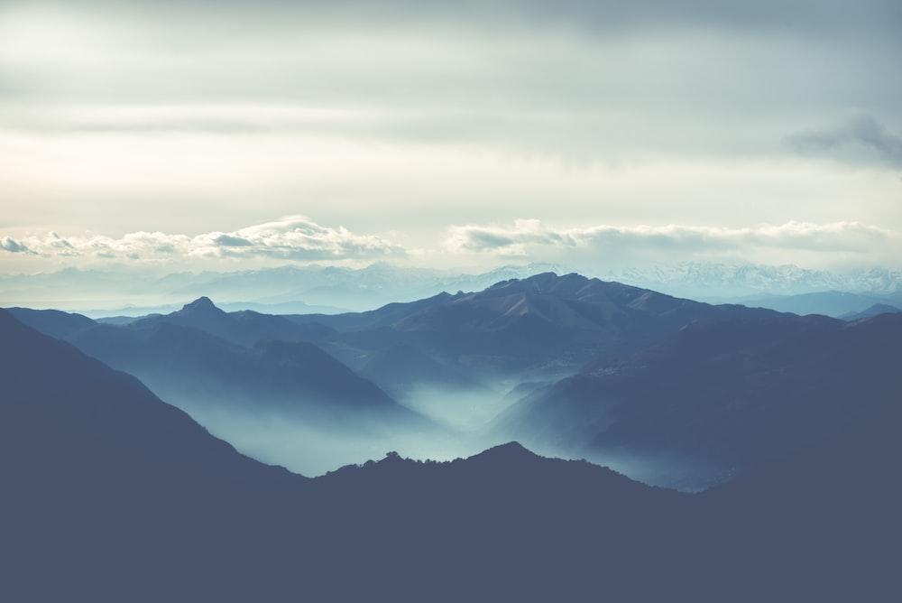black rocky mountain under white cloudy sky