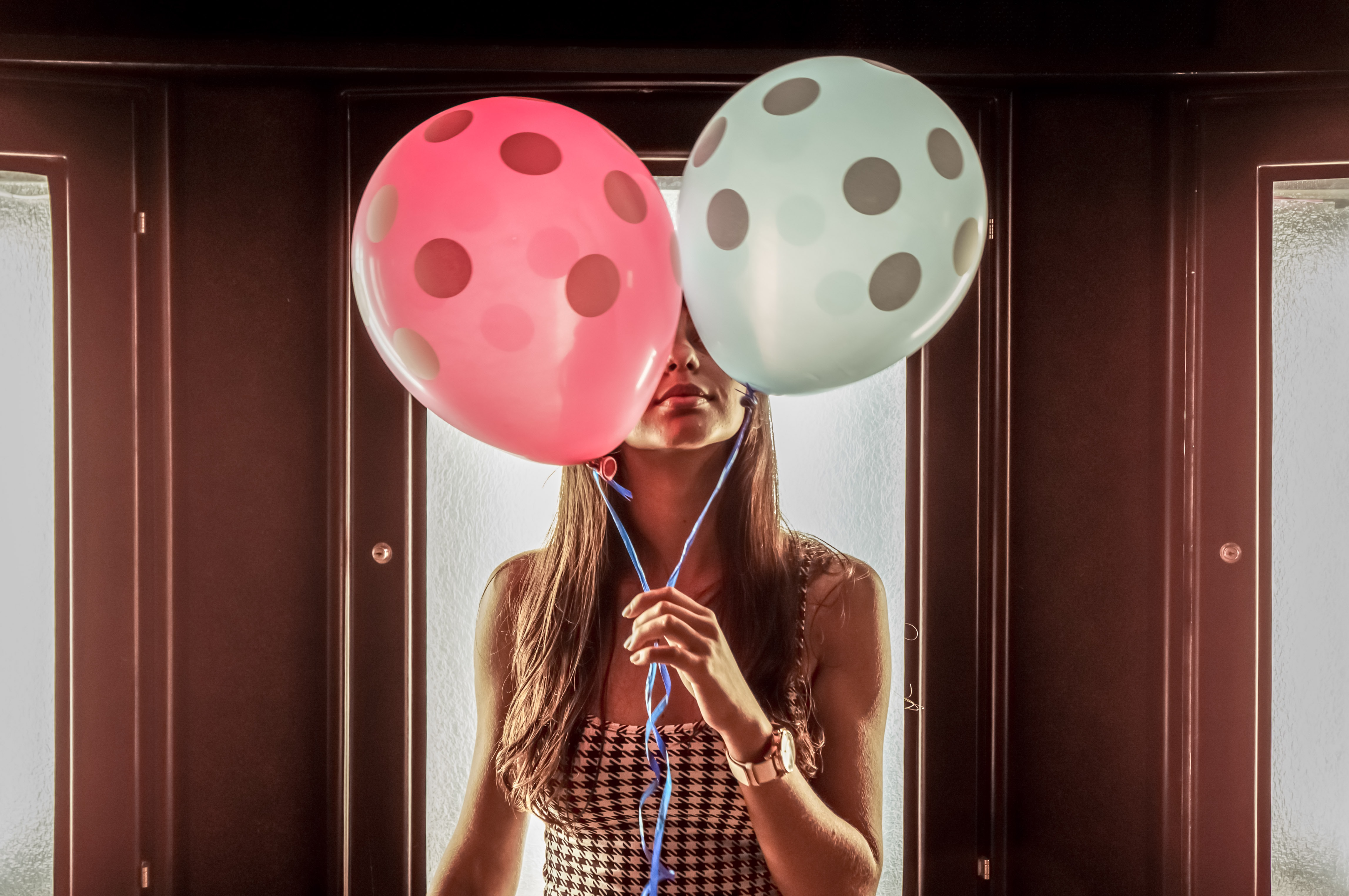 woman wearing white-and-black houndstooth tank dress holding pink and teal inflated balloons