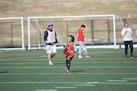 girl in orange tank top playing lacrosse during daytime