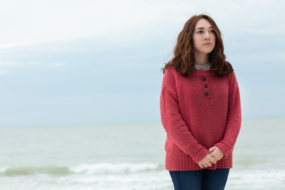 standing woman wearing red sweater and blue denim bottoms during daytime