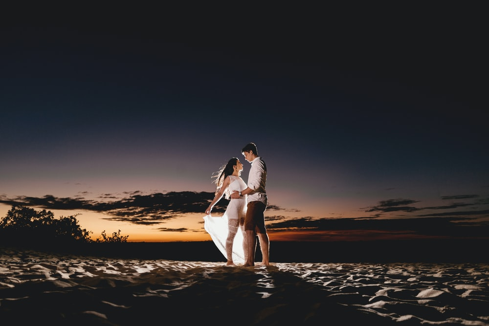 couple standing on beach sand during golden hour
