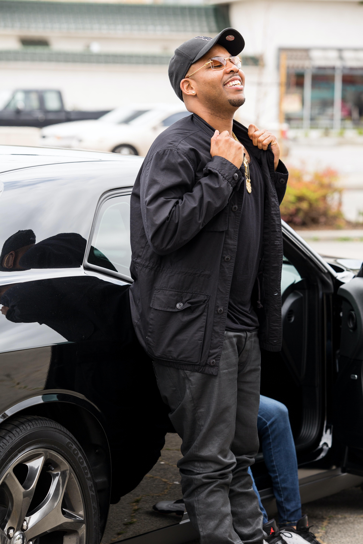 smiling man in black jacket leaning on car
