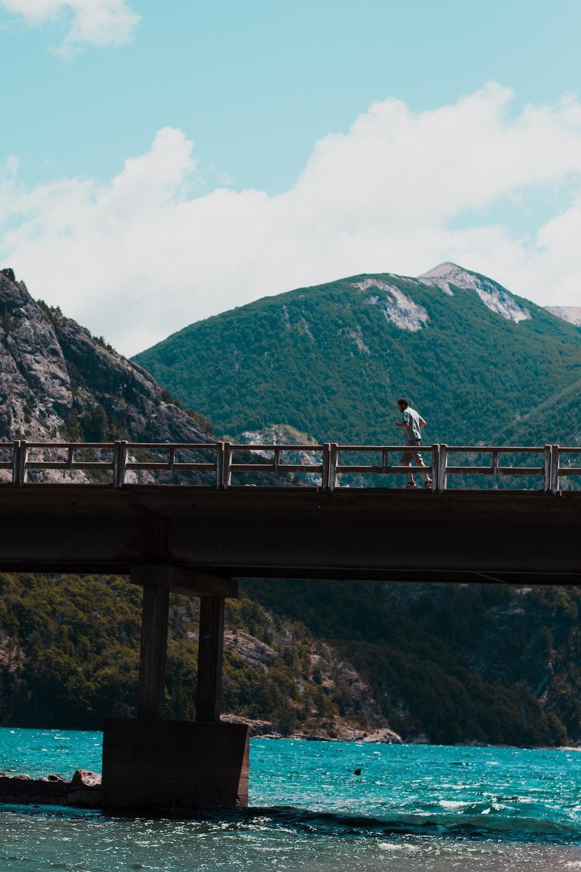 man running on concrete walk bridge above body of water during daytime