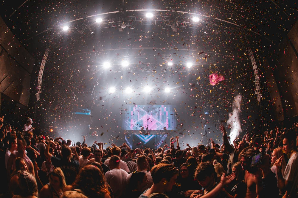 confetti falling from above at music performance with huge crowd