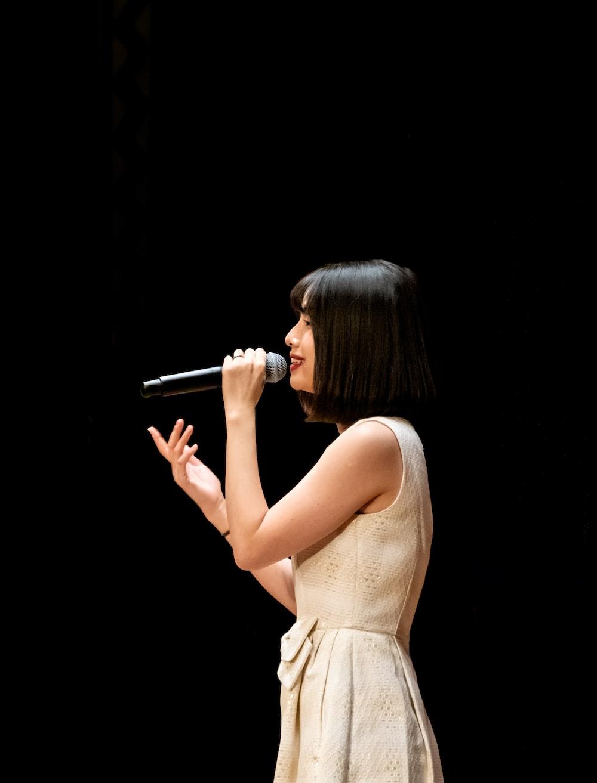 woman in white tank dress singing