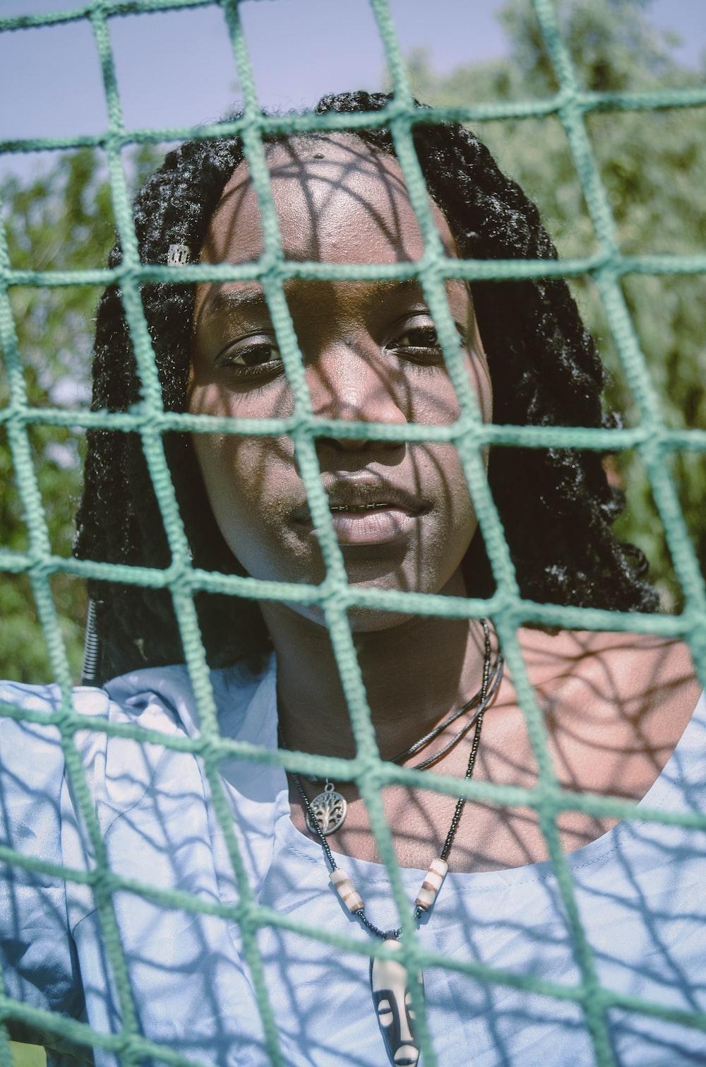 woman in blue scoop neck shirt through net