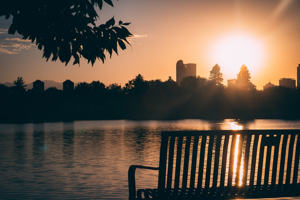 silhouette of bench near body of water during daytime