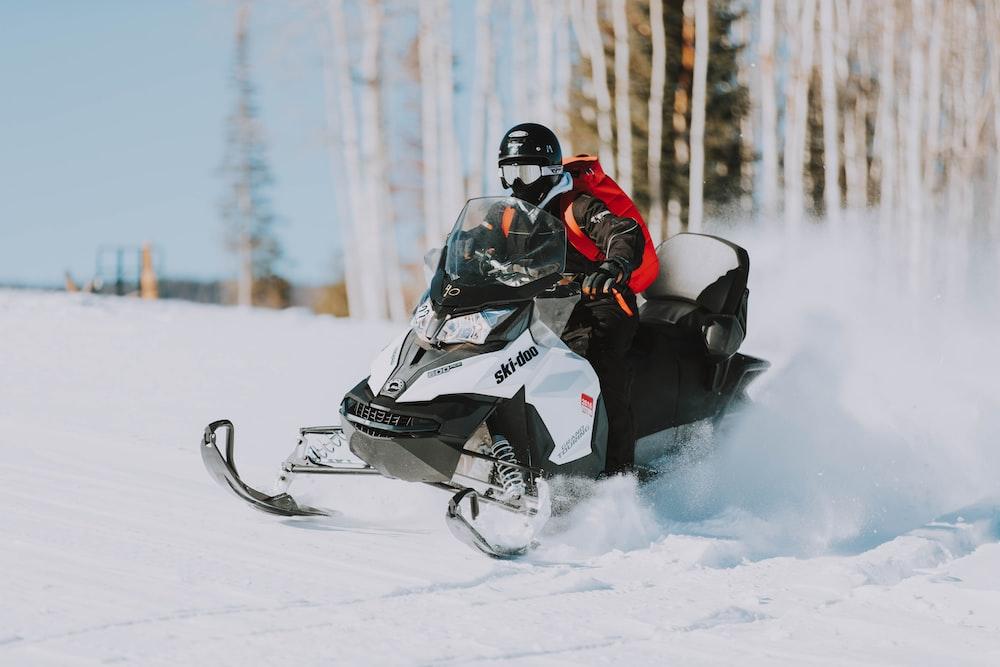 snowmobile speeding on snow near tree lines