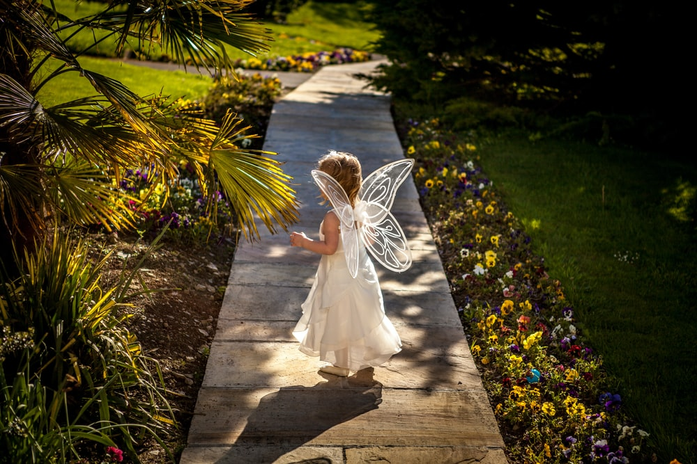 girl wearing angel costume standing on wooden pathway