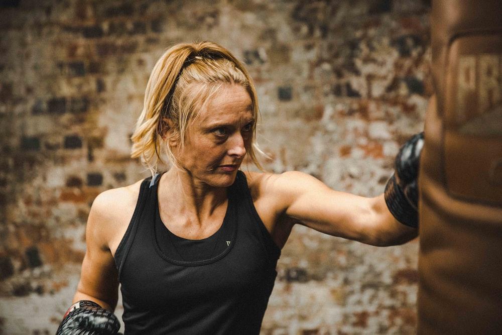 woman in black tank top punching brown heavy bag