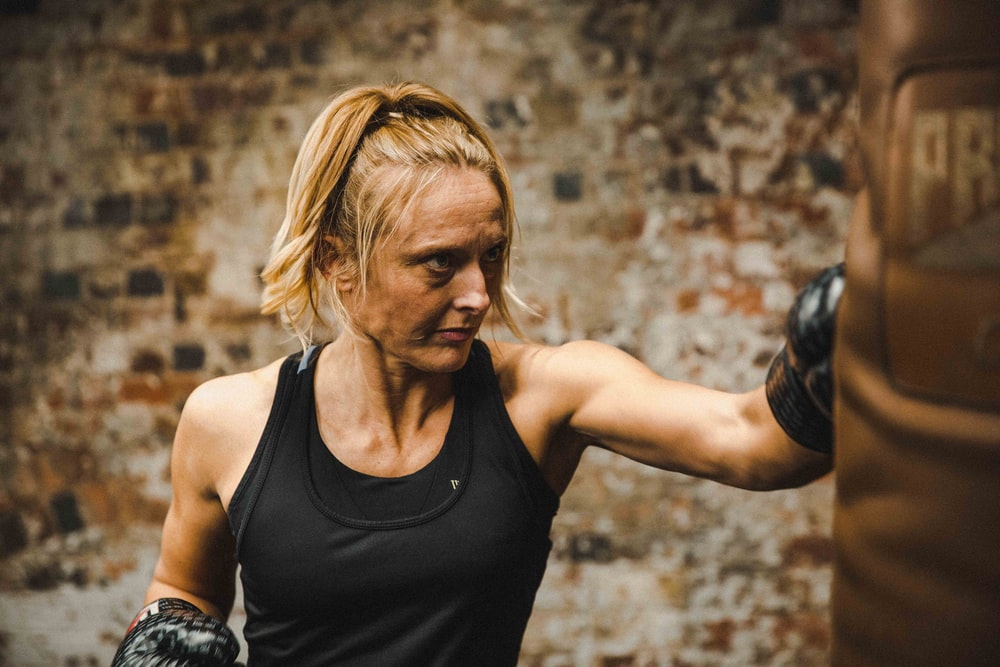 woman in black tank top punching brown heavy bag