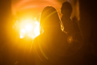 silhouette photography of woman in front of orange light luminescence teams background