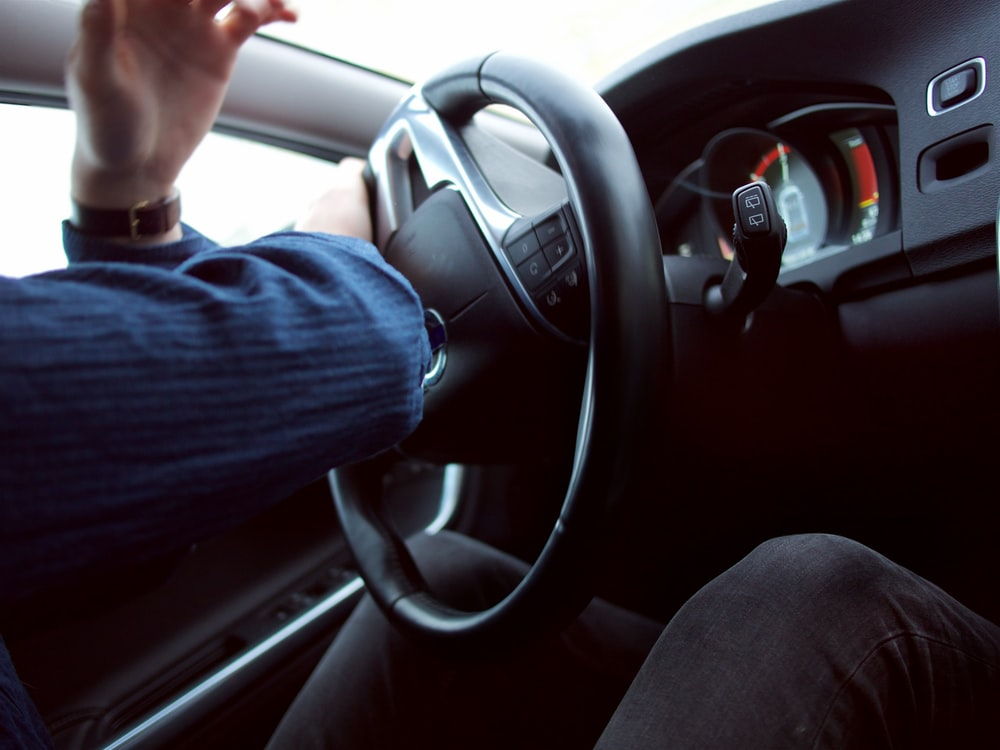 man holding black steering wheel