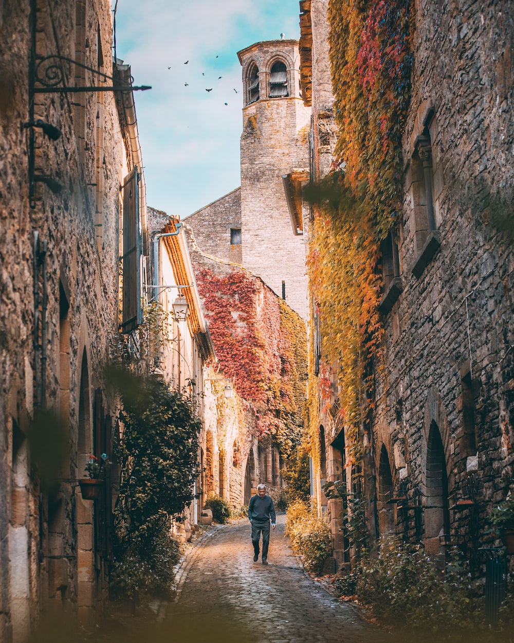man walking at alley between concrete buildings during daytime