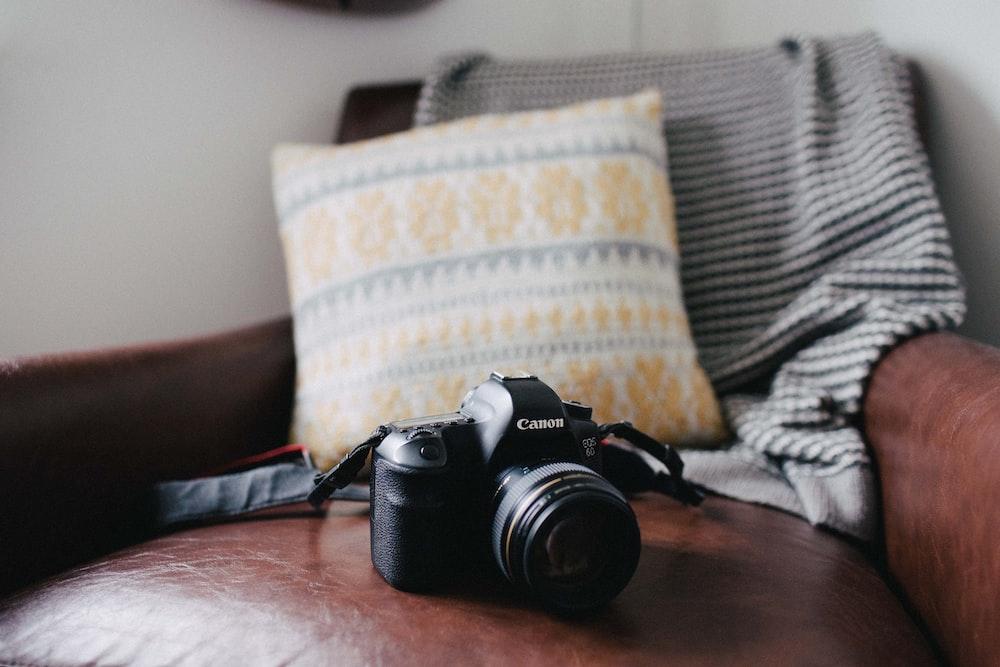 black Canon DSLR camera on brown leather sofa