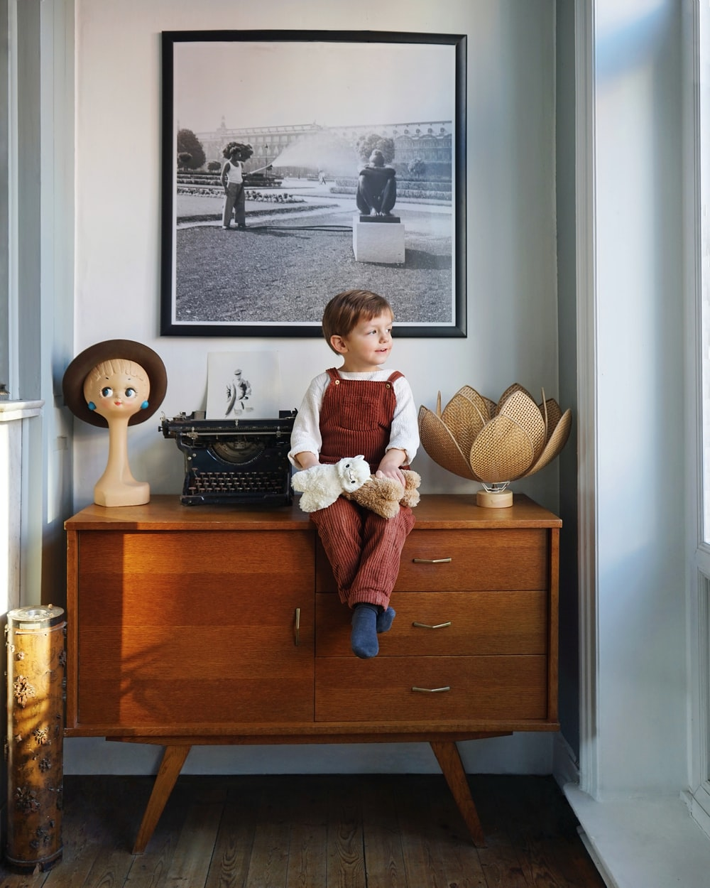 boy wearing red overalls sitting on brown wooden drawer