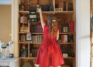 girl in re dress standing on stool while reaching books on shelve