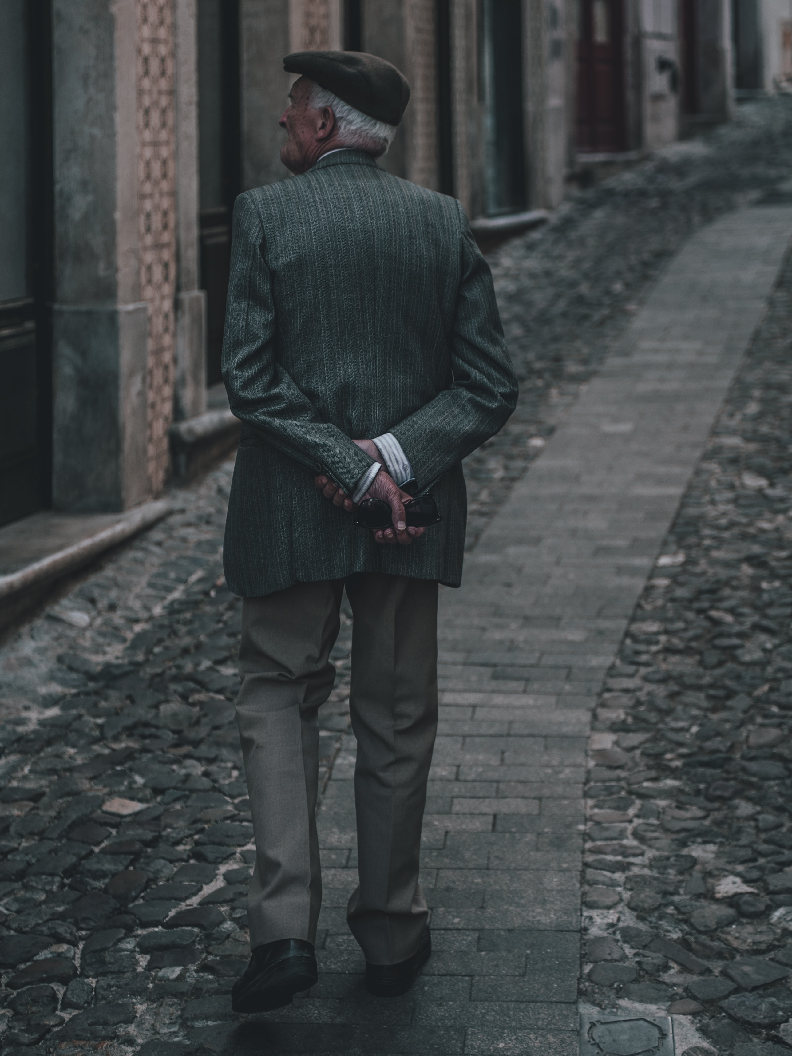 man in green coat walking on brick pavement in between concrete buildings during daytime