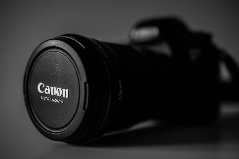 selective focus photography of black Canon Ultrasonic DSLR camera