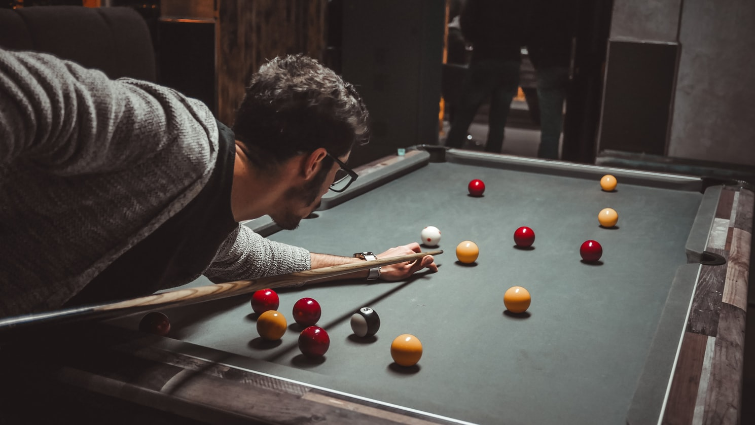 Man in gray sweater playing billiards