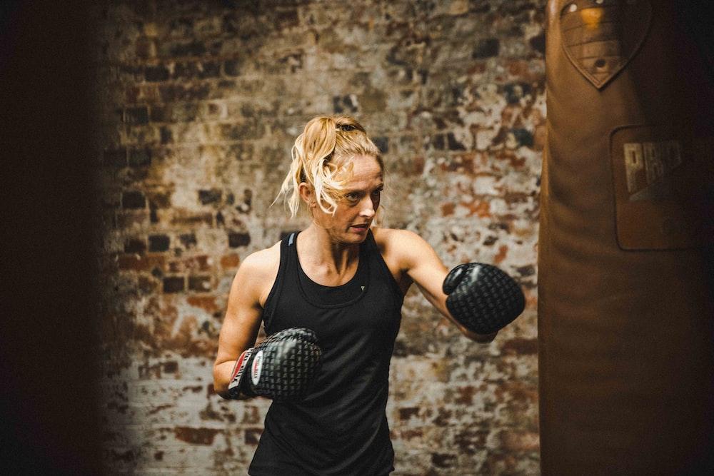 woman in black tank top wearing boxing gloves