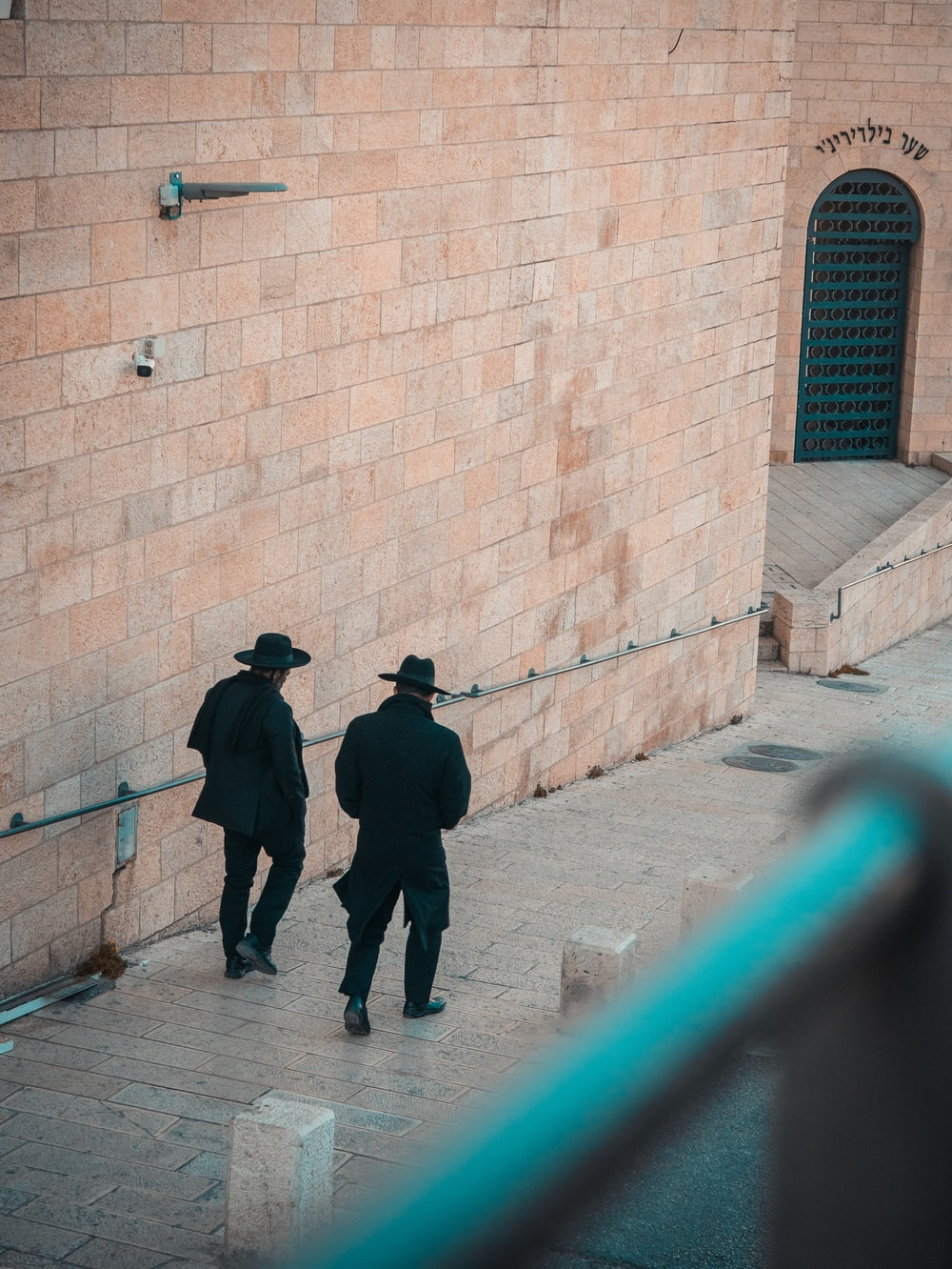 two person wearing black suit and hat walking on pathway