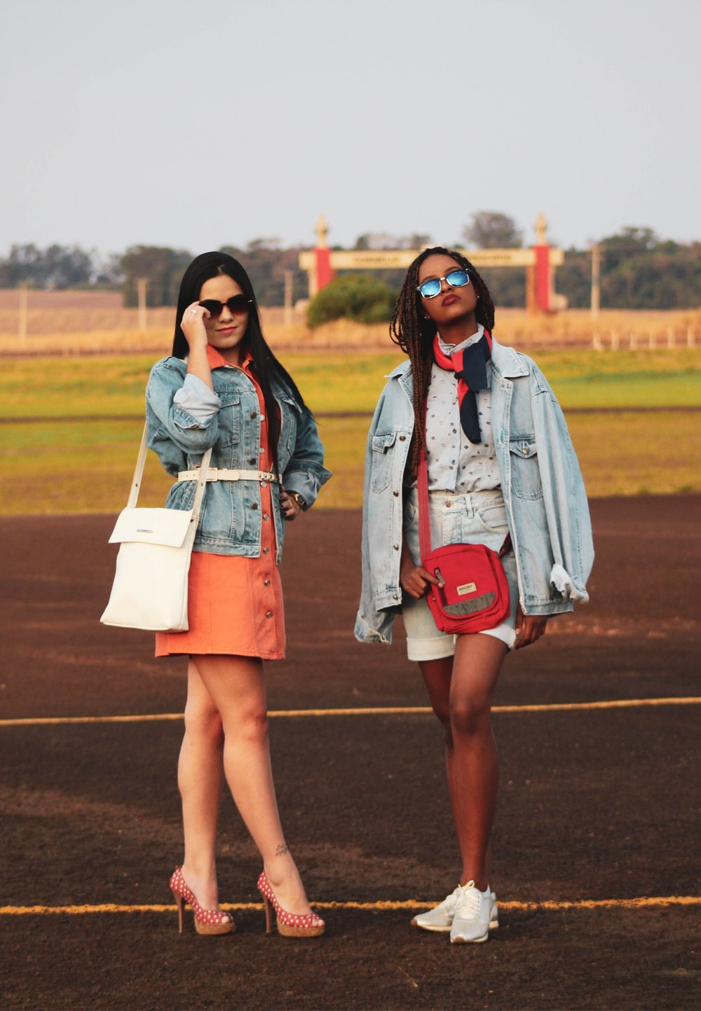 two women standing on sports field during daytime