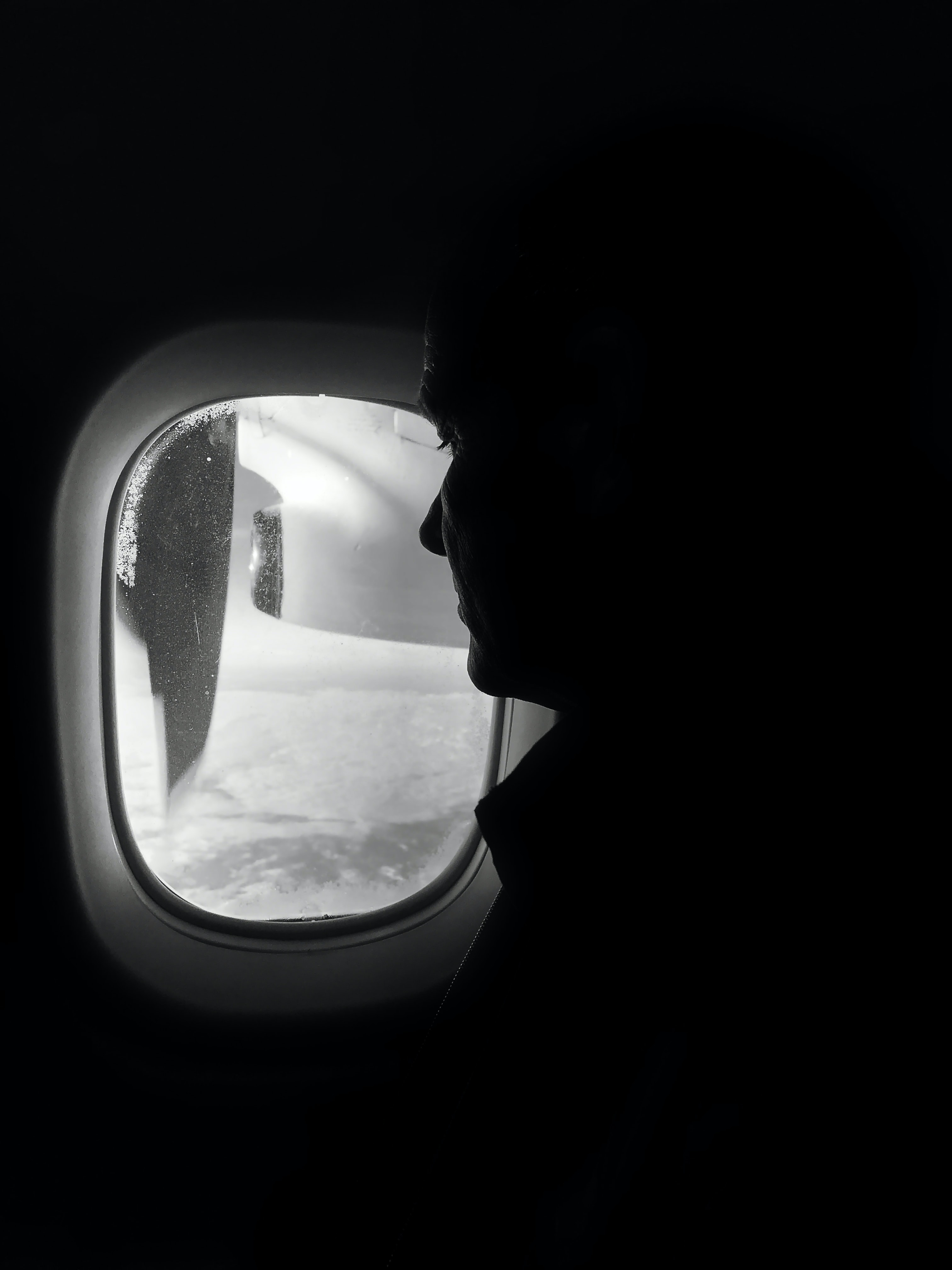 greyscale photo of person sitting inside plane