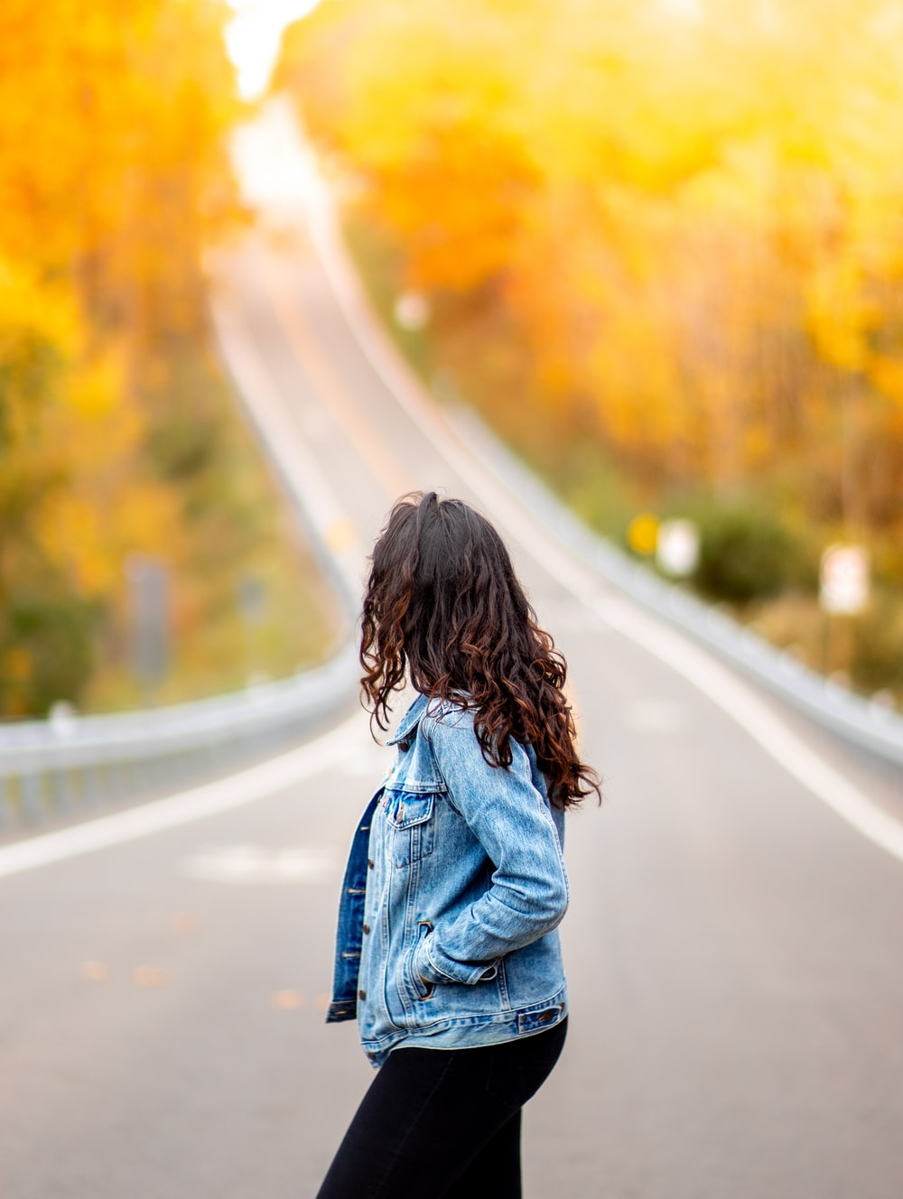 woman standing on road while hand in pocket during daytime