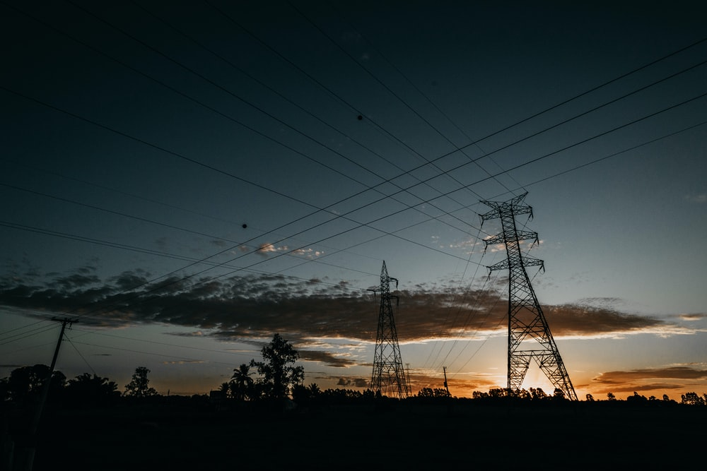 low-angle photography of transmission towers during golden hour