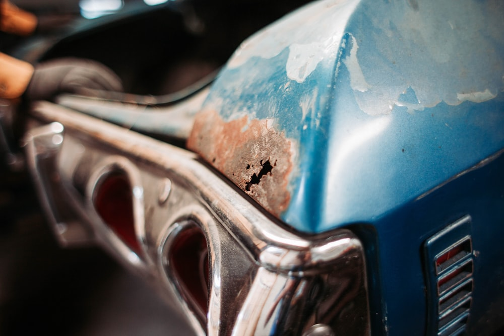closeup photography of classic blue car with rusted panels