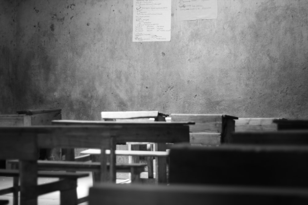 grayscale photography of school desk and board