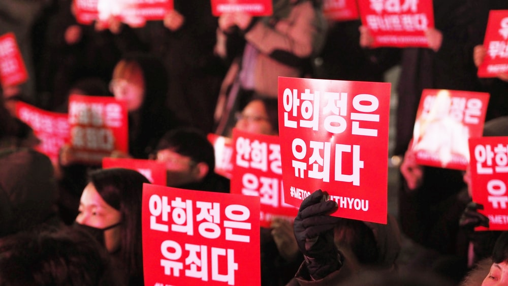people holding red signages
