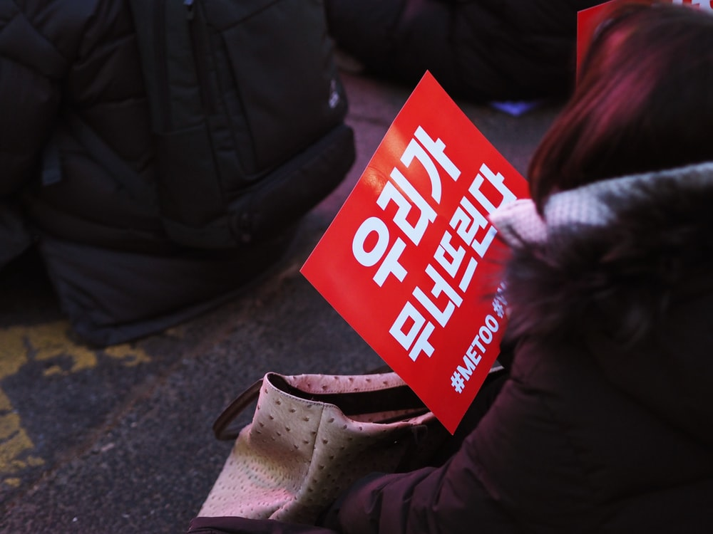 person holding red and white text signage