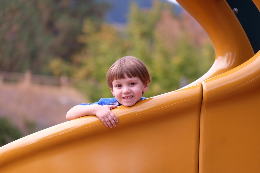 smiling boy sitting on orange slide during daytime